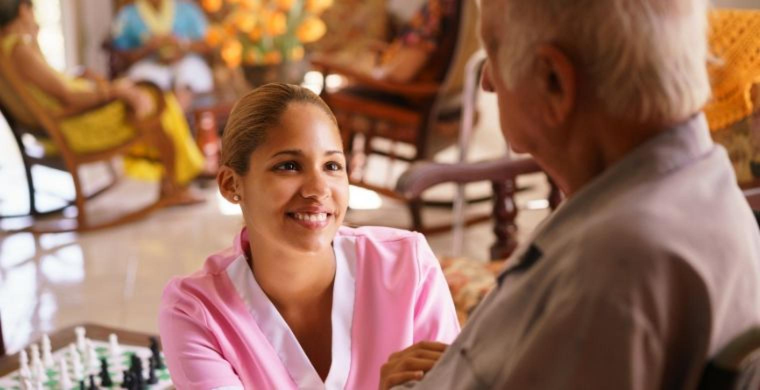 Young Hispanic Nurse Aid in Nursing Home with Elderly Man